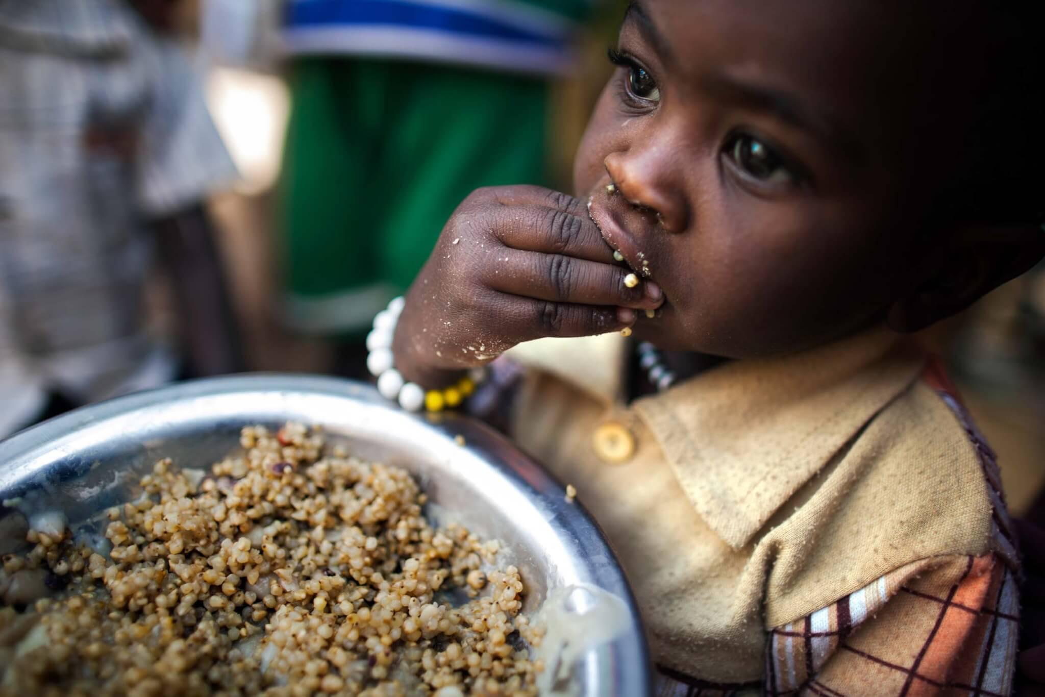 A child eats lentils in a food distribution centre, Rwanda