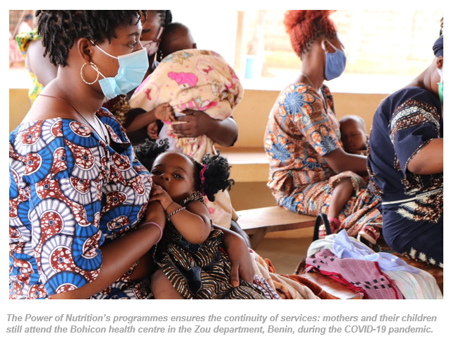 mothers and children at health clinic in benin wearing protective masks